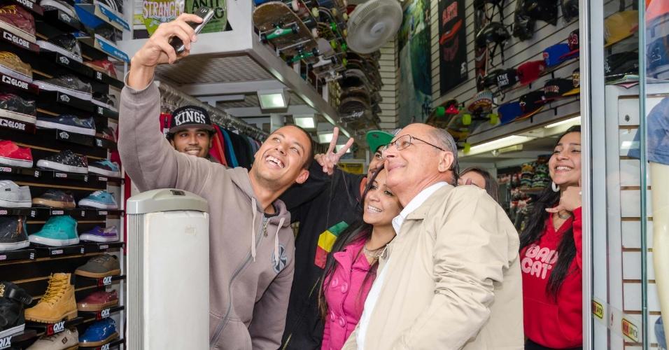 """4.out.2014 - O governador de São Paulo e candidato à reeleição, Geraldo Alckmin (PSDB), tira """"selfie"""" com eleitores em uma loja durante uma caminhada no calçadão de São Miguel Paulista, na região leste de São Paulo, neste sábado (4), véspera da eleição"""