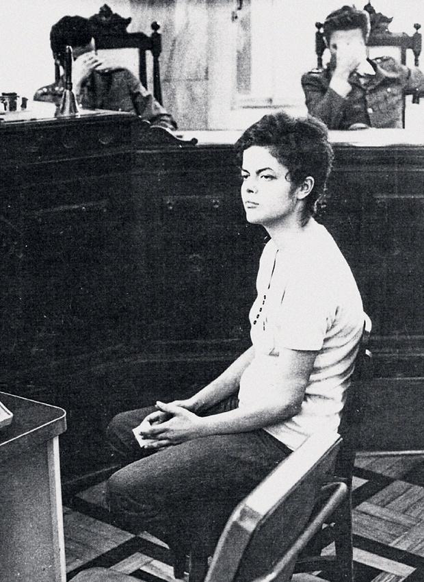 Dilma Rousseff participa de audiência na sede da Auditoria Militar no Rio de Janeiro, em novembro de 1970. Ela ficou presa durante quase dois anos em prisões em São Paulo, em Juiz de Fora (MG) e no Rio, onde passou por inúmeras sessões de depoimentos e torturas, como choques elétricos, palmatória espancamentos. Em depoimento ao Conselho de Direitos Humanos de Minas Gerais, Dilma contou as agressões lhe causaram hemorragias no útero e o comprometimento de parte de sua arcada dentária. ?As marcas da tortura sou eu, fazem parte de mim?, disse. Ao fundo, os oficiais que a interrogavam escondem o rosto