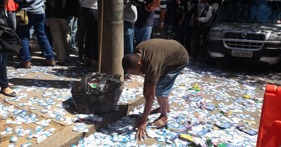 5.out.2014 - À espera da chegada do candidato à Presidência Aécio Neves (PSDB) e do candidato ao governo de Minas Gerais  Pimenta da Veiga (PSDB), homem limpa propaganda eleitoral do chão