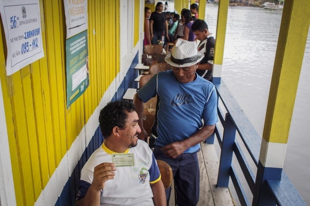 5.out.2014 - Eleitores fazem fila em posto de votação no lago do vilarejo Catalão, em Iranduba, no Amazonas, onde cerca de 400 pessoas vivem em mais de 100 casas flutuantes