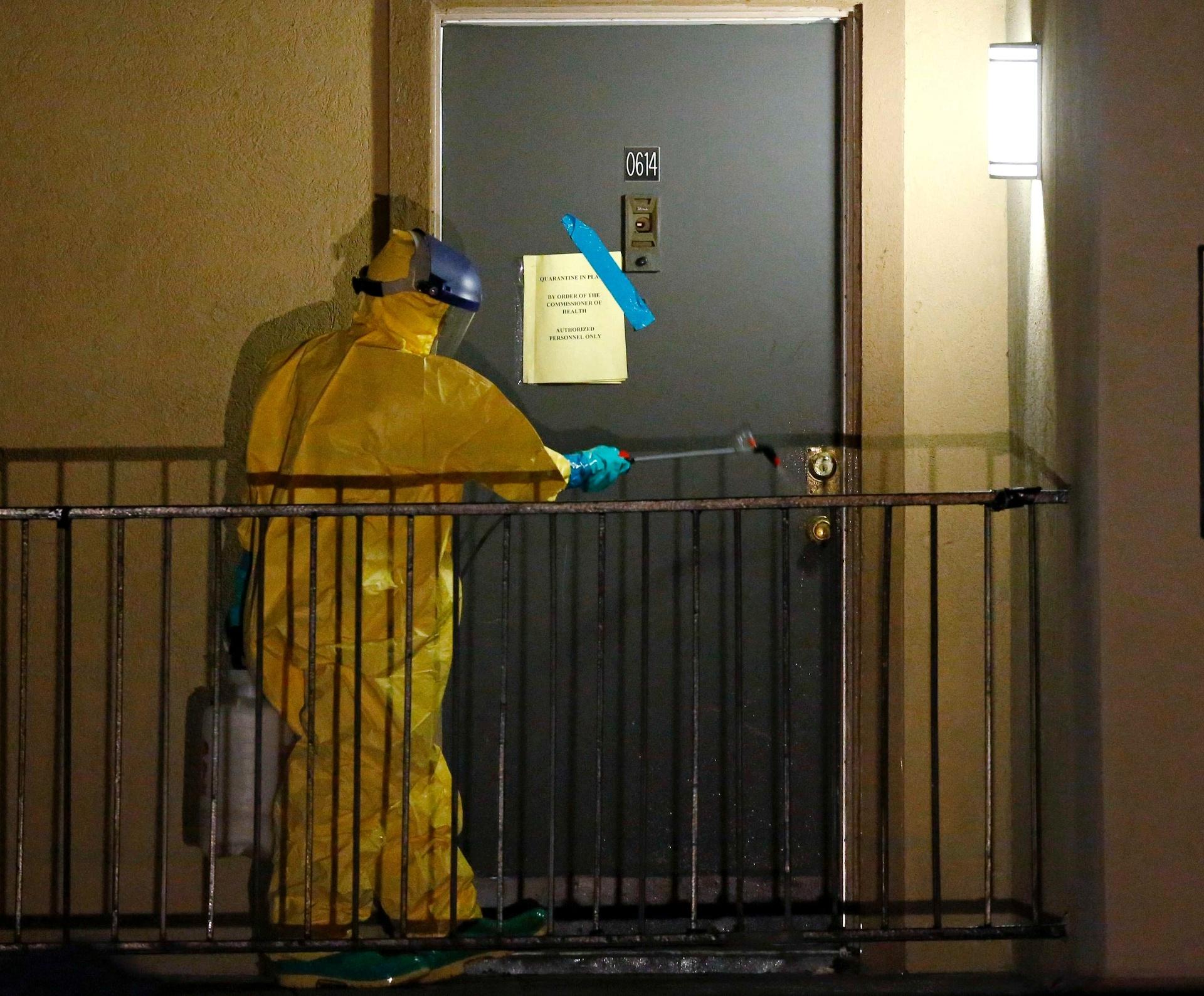 5.out.2014 - Funcionário de saúde pulveriza a porta do apartamento onde um norte-americano diagnosticado com o vírus ebola estava hospedado, em Dallas, Texas, na madrugada deste domingo (5). O estado de saúde do primeiro paciente com ebola diagnosticado nos EUA piorou neste sábado, passando de grave para crítico, enquanto permanece internado em Dallas. Enquanto isso, as autoridades de saúde rastreiam dezenas de possíveis casos nos EUA