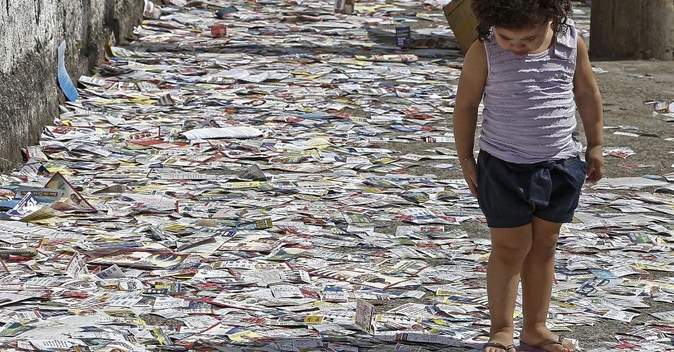 5.out.2014 - Menina olha para os santinhos jogados no chão próximo a uma seção eleitoral em São Paulo neste domingo (5). Mais de 142 milhões de brasileiros devem comparecer até o final do dia para votar