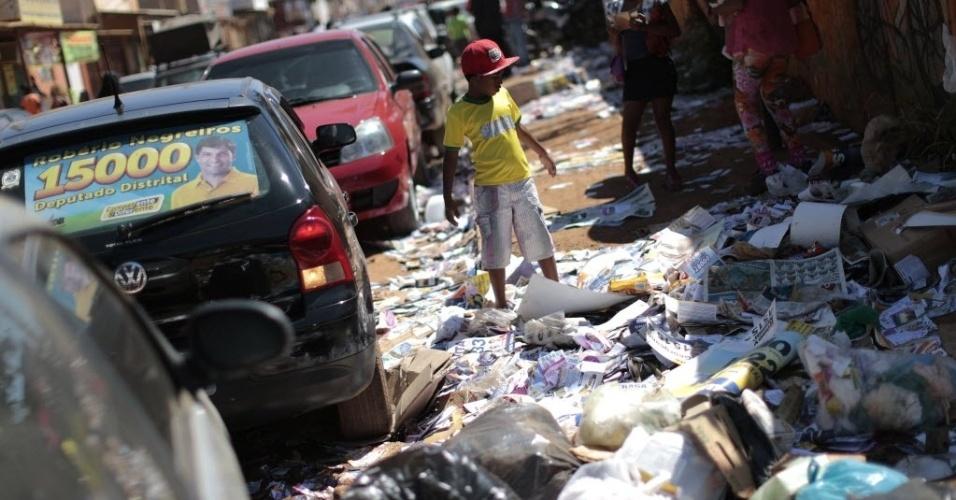 5.out.2014 - Menino caminha por uma calçada cheia de lixo e panfletos eleitorais no bairro de Ceilândia, na periferia de Brasília, neste domingo (5), dia do primeiro turno das eleições
