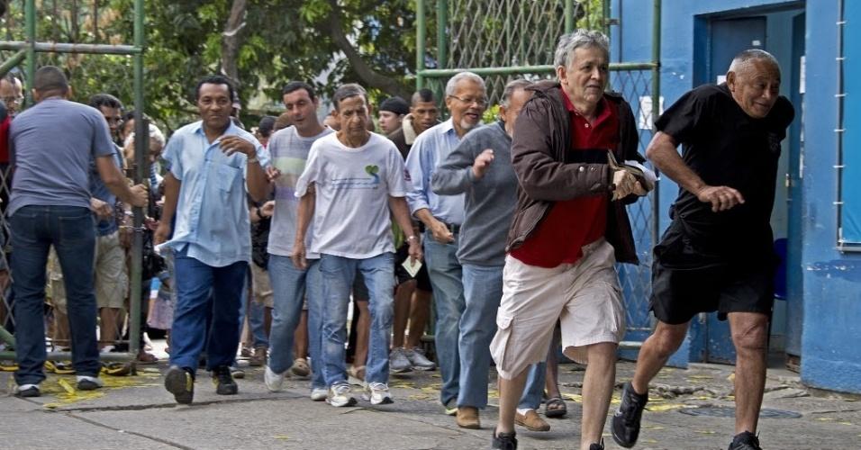 5.out.2014 - Pessoas correm na abertura de um distrito eleitoral na favela da Rocinha, no Rio de Janeiro, neste domingo (5)