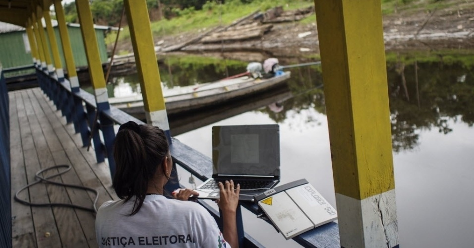 5.out.2014 - Um funcionário da Justiça Eleitoral utiliza transmissão via satélite em uma seção eleitoral no lago do vilarejo Catalão, em Iranduba, no Amazonas, onde cerca de 400 pessoas vivem em mais de 100 casas flutuantes