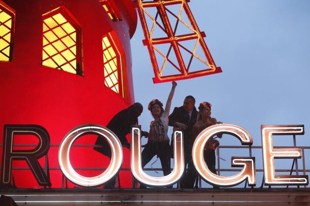 6.out.2014 - Ativistas do grupo feminista Femen são retiradas do telhado do cabaré Moulin Rouge (Moinho Vermelho, em francês), em Paris, capital francesa, nesta segunda-feira (6). Elas protestavam contra a indústria do sexo fem