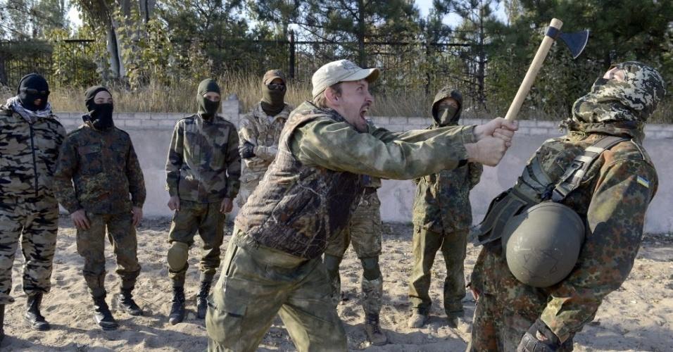 6.out.2014 - Membros de batalhão pró-Ucrânia participam de exercícios militares com um machado perto da cidade de Mariupol, no leste da Ucrânia, nesta segunda-feira (6)