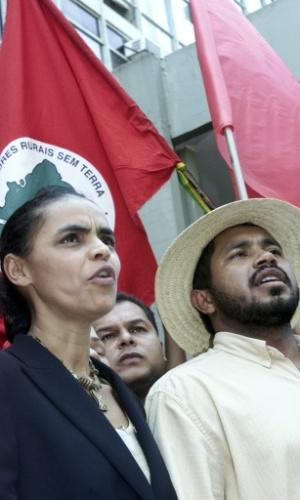 Marina Silva, ministra do Meio Ambiente do governo de Luiz Inácio Lula da Silva, canta o hino nacional ao lado do líder do MST (Movimento dos Trabalhadores sem Terra) durante protesto contra o uso de sementes trangênicas na agricultura brasileira, no dia 26 de setembro de 2003