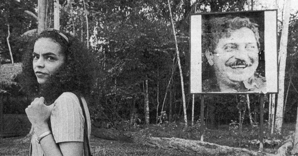 Marina Silva posa em frente a um cartaz com a foto de Chivo Mendes em Xapuri (AC), cidade onde morava o ambientalista, em 1995. Amigos e companheiros de militância, Marina e Chico levaram o Acre aos holofotes nacionais. A morte de Chico causou comoção em 1988, principalmente porque ele avisou que recebia constantes ameças de morte devido sua luta pela preservação da Amazônia, mas não recebeu atenção
