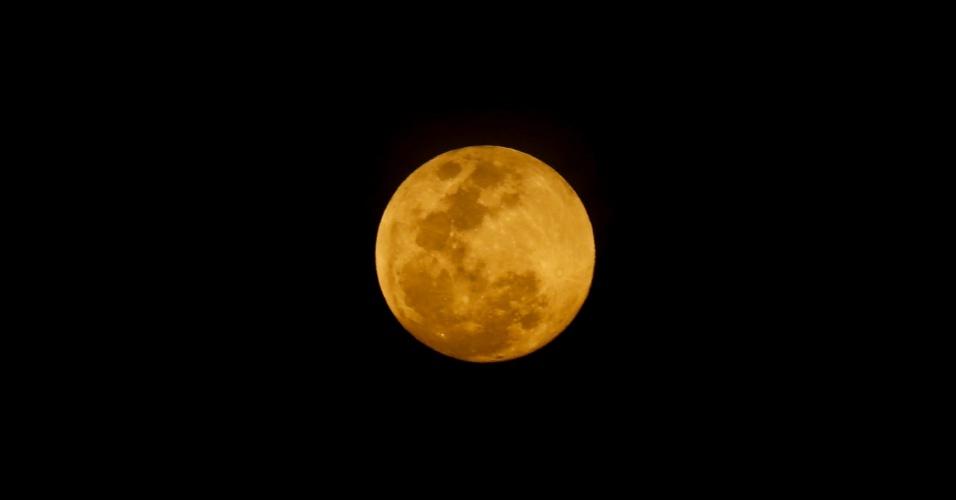 7.out.2014 - A lua cheia é revista da região da Serra da Cantareira, na zona norte de São Paulo, na noite desta terça-feira (7)