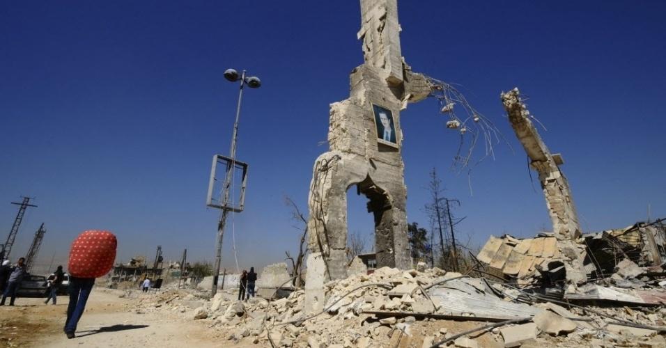 7.out.2014 - Fotografia do ditador da Síria, Bashar al-Assad, é vista em escombros na entrada do bairro al-Dukhaneya, em Damasco, nesta terça-feira (7). Civis recuperam pertences de suas casas após soldados leais ao presidente terem recuperado controle da área dos rebeldes