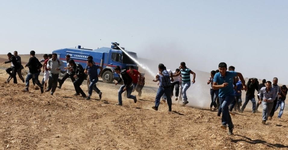 7.out.2014 - Povo curdo foge de jato de água durante manifestação para questionar as condições dos moradores de Kobani, cidade próxima da fronteira entre a Síria e Turquia, nesta terça-feira (7). Combatentes do grupo Estado Islâmico (EI) avançaram para o sudoeste da cidade curda durante a noite, afirmou nessa terça a ONG Observatóroio Sírio de Direitos Humanos, que está monitorando o conflito. A perspectiva de que Kobani caia em mãos dos militantes que a cercam há três semanas aumentou a pressão sobre a Turquia para se juntar a uma coalizão internacional liderada pelos EUA que combate o EI