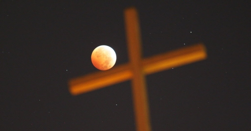 8.out.2014 - A lua vermelha iluminou uma cruz em Los Angeles, na Califórnia, Estados Unidos, na madrugada desta quarta-feira (8). O fenômeno foi apelidado de