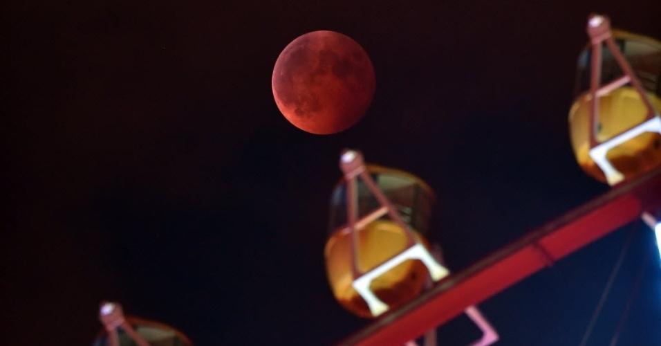 8.out.2014 - Entusiastas andaram de roda-gigante para admirar a lua avermelhada no céu de Tóquio, no Japão, nesta quarta-feira (8). O fenômeno foi apelidado de