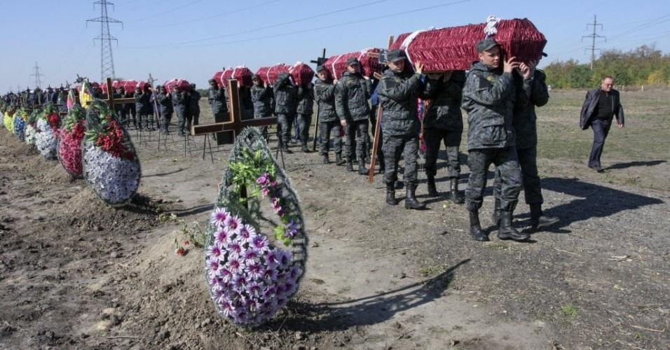 8.out.2014 - Membros da Guarda Nacional carregam caixões durante um funeral de soldados não identificados das forças militares pró-Ucrânia, que morreram ao tomar parte no conflito na região leste, em um cemitério em Dnipropetrovsk (a quarta maior cidade do país), nesta quarta-feira (8)