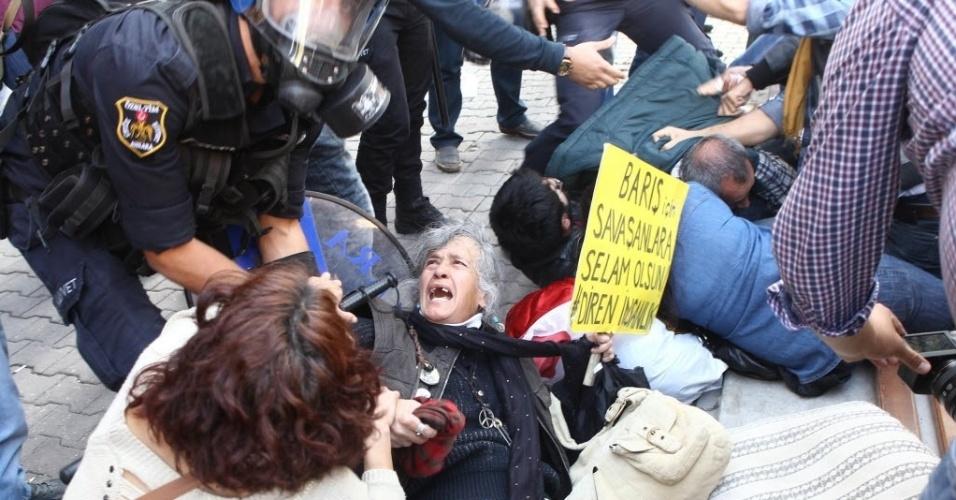8.out.2014 - Oficiais de polícia tentam segurar manifestante nesta terça-feira (7) em Ancara, na Turquia, durante protesto contra os ataques lançados por grupos do Estado Islâmico na cidade síria de Kobani. Os curdos denunciavam a recusa do governo de Ancara de intervir militarmente para impedir a queda da cidade síria de Kobane, de acordo com a imprensa turca