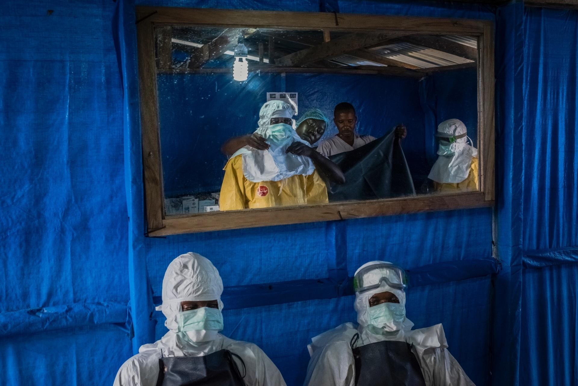 Enfermeiros recebem ajuda para colocar roupas protetoras antes de entrar na área de alto risco onde são tratados doentes com ebola na Unidade de Tratamento de Ebola no Condado de Bong em Sgt. Kollie Tow, na Libéria