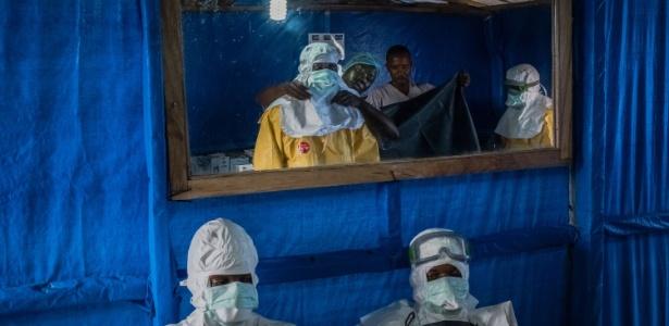Enfermeiros recebem ajuda para colocar roupas protetoras em clínica que trata doentes com ebola na Libéria; espelho ajuda a conferir se não há pele exposta - Daniel Berehulak/The New York Times