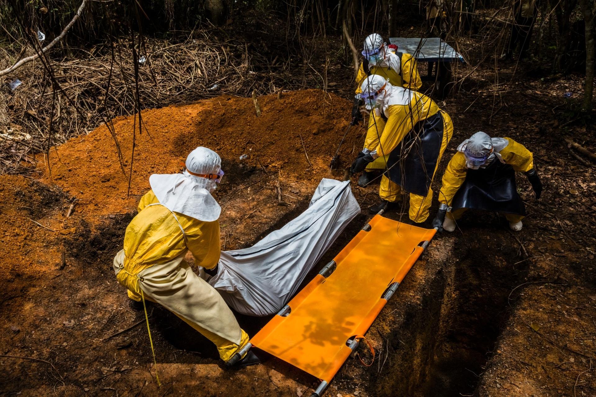 Equipe funerária enterra o corpo de Robert Yini, que contraiu ebola, em uma cova adjacente à Unidade de Tratamento de Ebola no Condado de Bong em Sgt. Kollie Tow, na Libéria