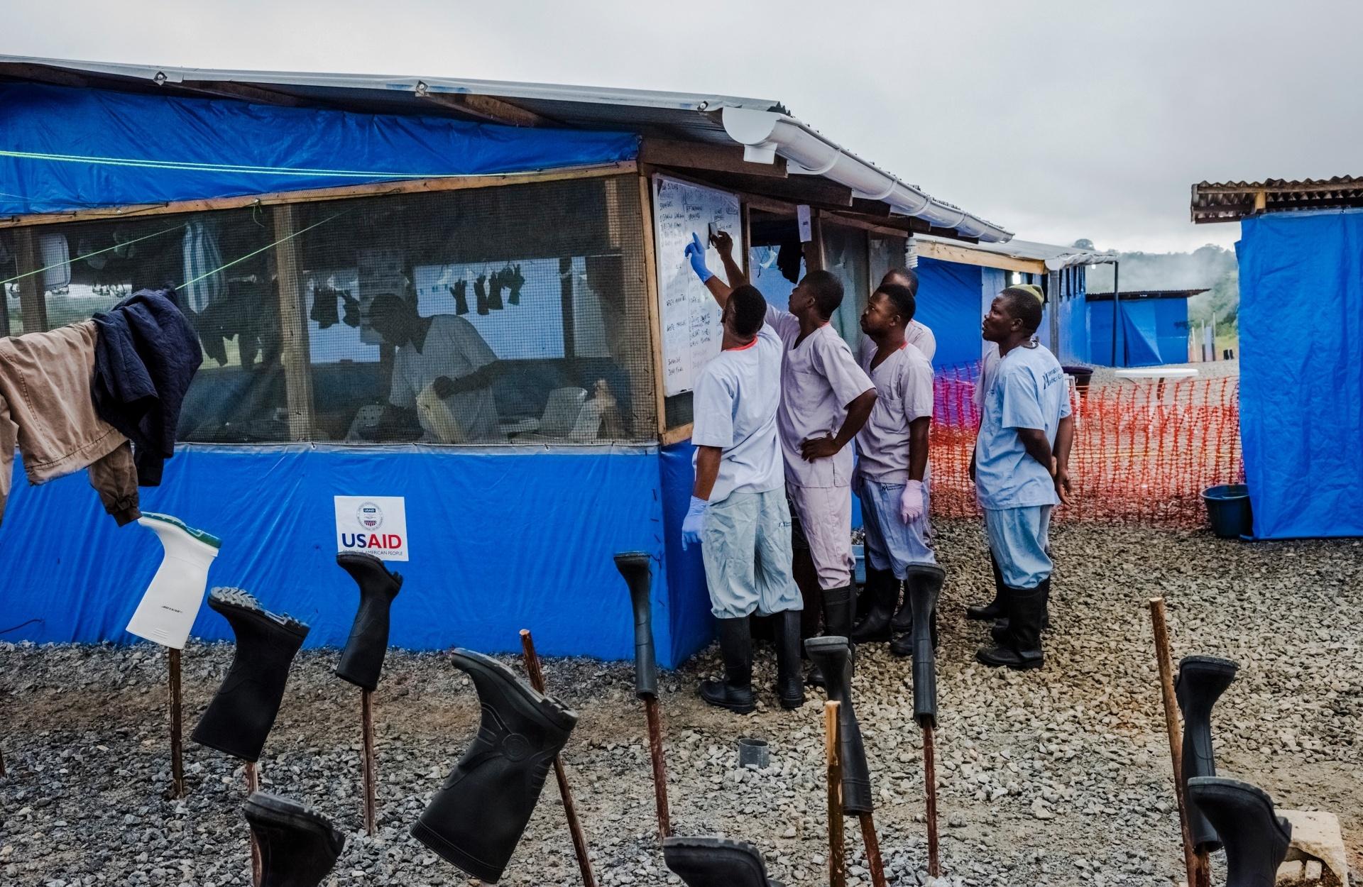 Funcionários da Unidade de Tratamento de Ebola no Condado de Bong em Sgt. Kollie Tow, na Libéria, planejam o cronograma de desinfecção de materiais