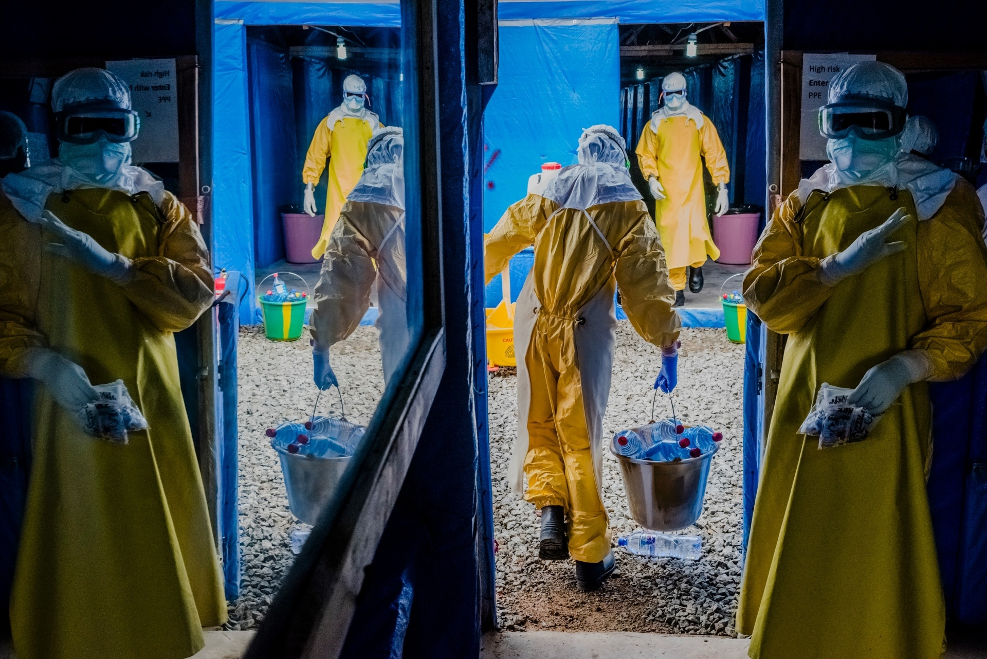 Funcionários entram em zona de alto risco durante o turno da manhã na Unidade de Tratamento de Ebola no Condado de Bong em Sgt. Kollie Tow, na Libéria. O centro recém-aberto é operado por uma organização de caridade norte-americana, a International Medical Corps. Voluntários ocidentais e liberianos identificam quem está infectados e tentam evitar que o vírus se espalhe