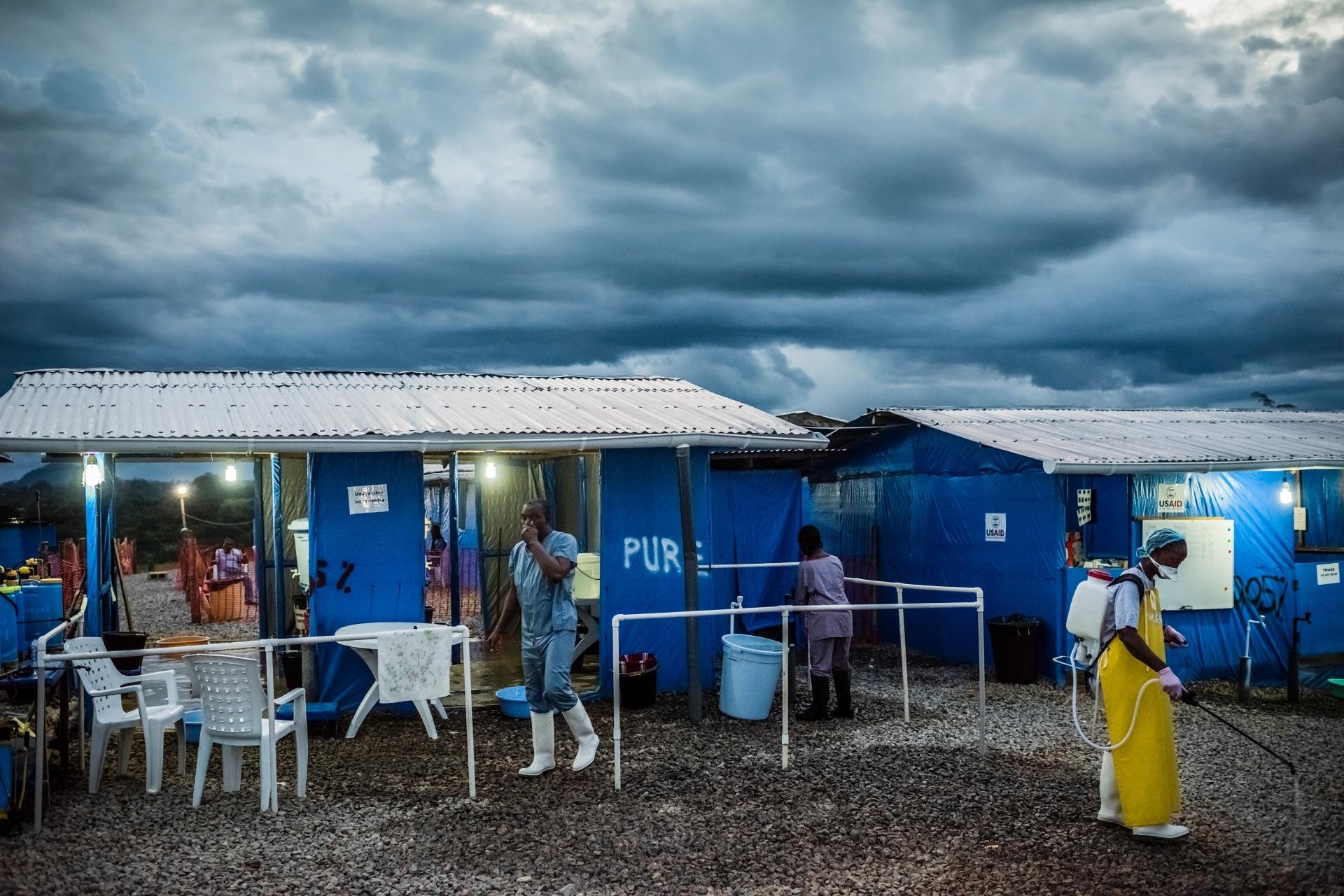 Homem desinfeta rosto depois de deixar área de alto risco onde são tratados doentes com ebola na Unidade de Tratamento de Ebola no Condado de Bong em Sgt. Kollie Tow, na Libéria