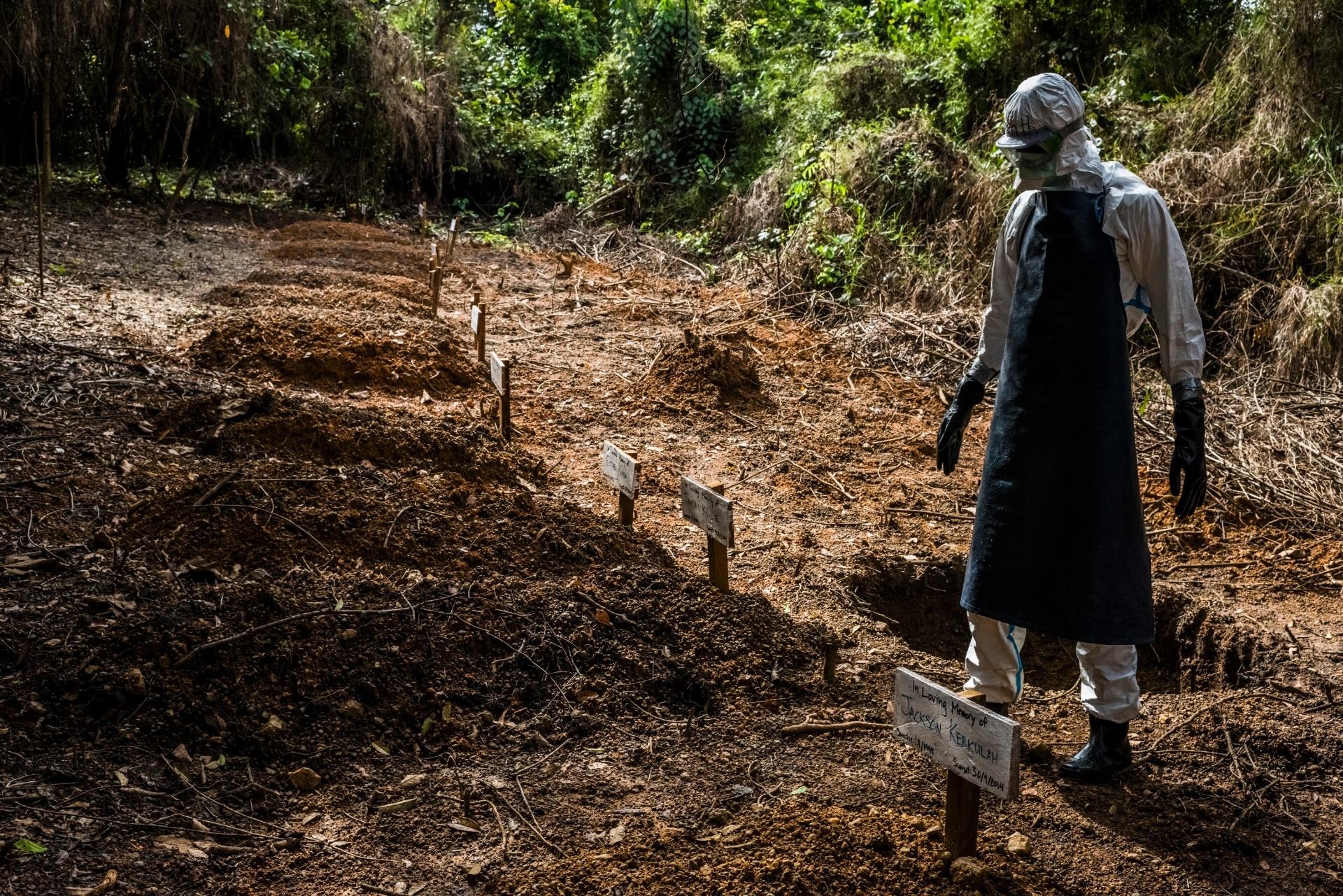 Membro da equipe funerária caminha por covas onde são enterradas vítimas do ebola, próximas à Unidade de Tratamento de Ebola no Condado de Bong em Sgt. Kollie Tow, na Libéria. O centro -- que tem uma área de triagem, uma restrita para suspeitos de infecção e outra para tratamento dos doentes -- não está lotado como outras clínicas na Monróvia