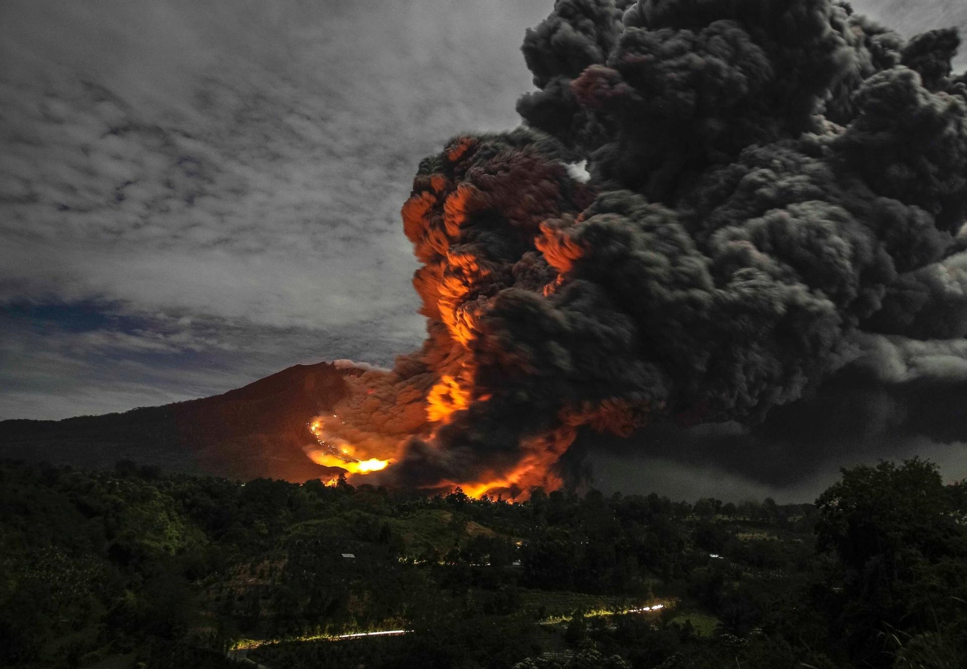 8.out.2014 - O monte Sinabung expele lava e fumaça nesta quarta-feira (8), visto da aldeia Tiga Pancur, na província de Sumatra do Norte, na Indonésia. O vulcão entrou em erupção em agosto de 2010 pela primeira vez em 400 anos, e está ativo desde setembro. Ao menos 16 pessoas morreram em decorrência da atividade vulcânica neste ano e mais de 25 mil tiveram que ser evacuadas