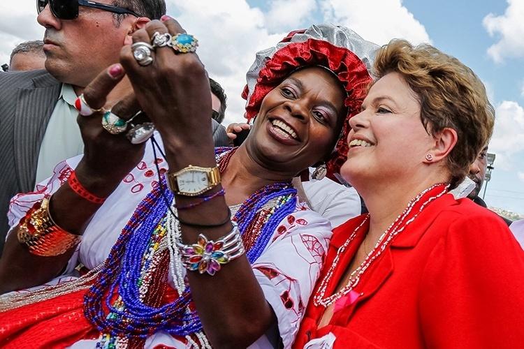 9.out.2014 - A presidente e candidata à reeleição, Dilma Rousseff (PT), tira foto com mulher vestida de baiana durante visita a Igreja do Bonfim, em Salvador (BA). Depois de entrevista a rádios locais, Dilma seguiu para o Museu do Ritmo, no bairro do Comércio, onde participou de um encontro com prefeitos e outras lideranças. Em seguida, Dilma foi para o Largo de Roma e chegou a entrar no santuário dedicado a Irmã Dulce. Para chegar à igreja do Bonfim, a presidente usou um carro aberto, ao lado do governador Jaques Wagner; do governador eleito Rui Costa, ambos do PT; e Otto Alencar (PSD), senador eleito da chapa petista