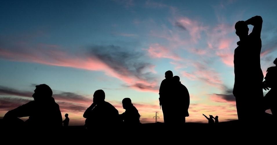 9.out.2014 - Curdos se sentam para ver o céu da cidade síria de Kobani, que fica próxima a fronteira entre a Síria e a Turquia, após ataques aéreos na quarta-feira (8). Os combatentes do grupo Estado Islâmico (EI) se apoderaram de mais de um terço da cidade fronteiriça, apesar de ataques aéreos liderados pelos Estados Unidos contra suas bases dentro e no entorno da área, majoritariamente curda, de acordo com grupo de monitoramento do conflito