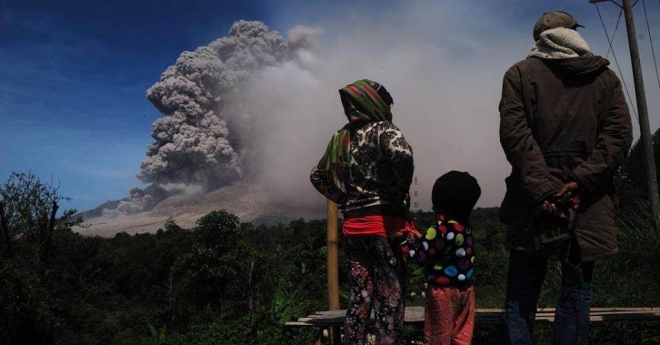 9.out.2014 - Moradores observam as nuvens cinzas que sobem da cratera do vulcão no Monte Sinabung, nesta quinta-feira (9), na ilha de Sumatra, na Indonésia. O vulcão entrou em erupção em agosto de 2010 pela primeira vez em 400 anos, e está ativo desde setembro. Ao menos 16 pessoas morreram em decorrência das erupções neste ano e mais de 25 mil tiveram que ser evacuadas
