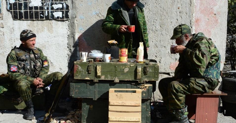 9.out.2014 - Soldados separatistas pró-Rússia fazem pausa perto do aeroporto internacional de Donetsk, na Ucrânia, onde continua a luta entre forças ucranianas e russas nesta quinta-feira (9). Cinco civis e um militar morreram nas últimas 24 horas em Donetsk durante os combates entre o exército ucraniano e os insurgentes pró-Rússia, apesar da trégua decretada há um mês, de acordo com a Prefeitura