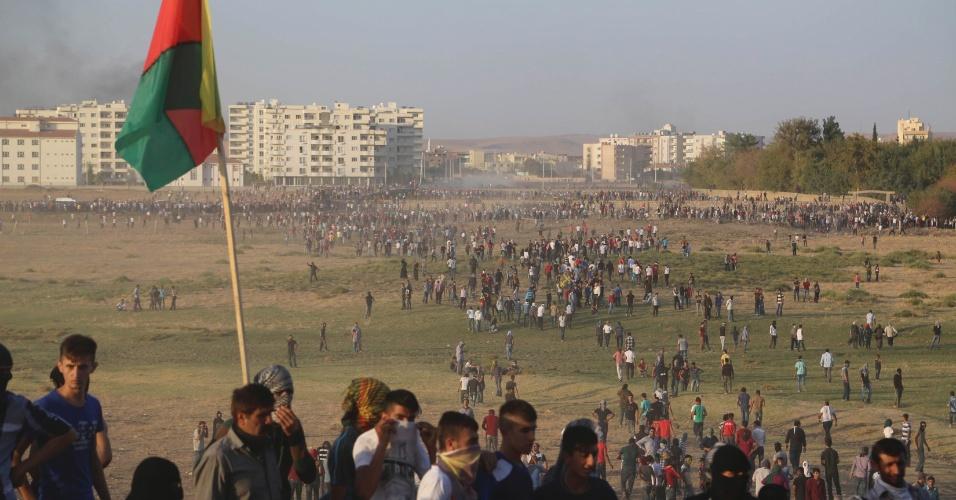 9.out.2014 - Manifestantes curdos protegem o rosto do gás lacrimogêneo usado por soldados turcos para dispersar um protesto que pedia um esforço maior do governo da Turquia para ajudar a cidade de síria de Kobani. Militantes do Estado Islâmico assumiram o controle de mais de um terço da cidade, apesar dos bombardeios liderados pelos Estados Unidos na tentativa de conter o avanço do grupo extremista