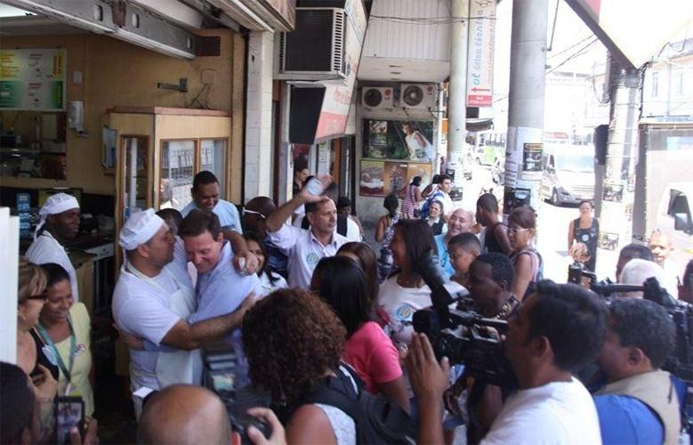 10.out.2014 - O candidato ao governo pelo PRB, Marcelo Crivella, abraça popular durante caminhada em São João de Meriti