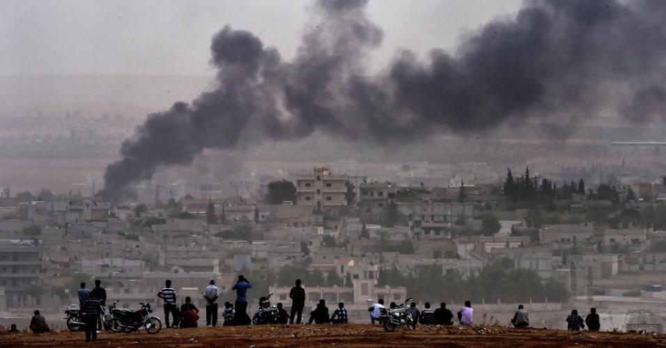 11.out.2014 - Curdos assistem a bombardeios na cidade de Kobani, na fronteira entre Síria e Turquia. O Estado Islâmico tenta avançar na cidade, mas sofre ataques da coalização militar liderada pelos Estados Unidos