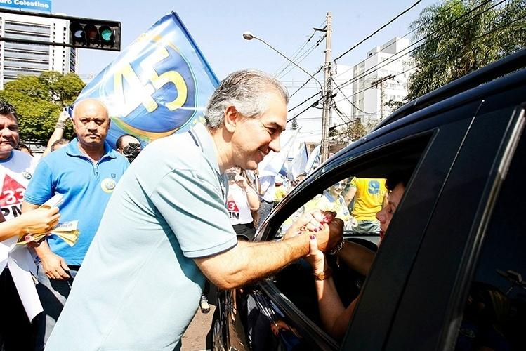 12.out.2014 - O candidato do PSDB ao governo do Mato Grosso do Sul, Reinaldo Azambuja, cumprimenta motorista durante caminhada pela região central de Campo Grande