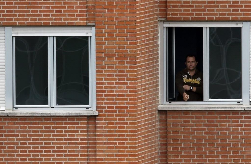13.out.2014 - Javier Limon Romero, marido de Teresa Romero Ramos, a enfermeira espanhola que contraiu ebola, olha para fora da janela de seu quarto, localizado em ala de isolamento no quinto andar do Hospital Carlos 3º de Madrid, onde ele é mantido em quarentena
