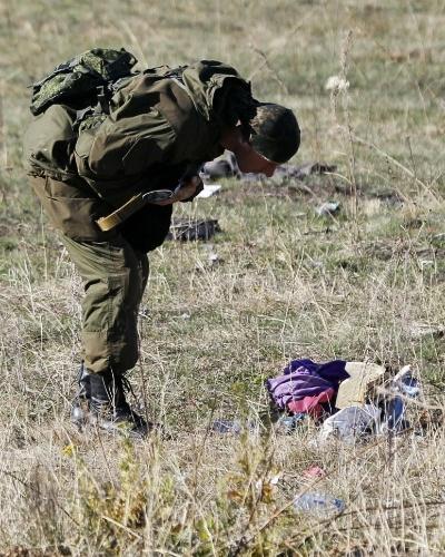 13.out.2014 - Militante de Donetsk, na Ucrânia, observa, nesta segunda-feira (13), objetos de passageiros do voo MH17 da Malaysia Airlines derrubado em julho. De acordo com a imprensa holandesa, os pertences que ainda estão no local do acidente serão enviados para os familiares dos passageiros