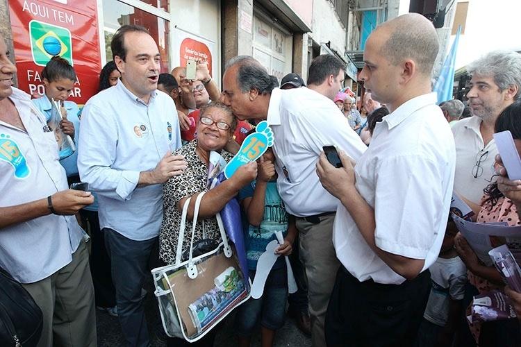 13.out.2014 - O governador e candidato à reeleição pelo PMDB, Luiz Fernando Pezão, beija cabeça de eleitora na estação do BRT e no mercadão de Madureira, em Madureira, zona norte do Rio de Janeiro