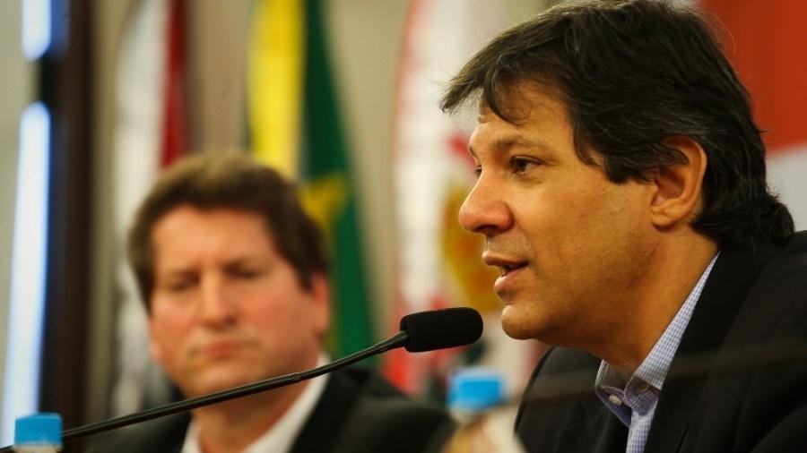 Tatto (esq.) observa Haddad durante pronunciamento à imprensa em 2014, quando ambos estavam na Prefeitura de São Paulo - Zanone Fraissat - 13.out.2014/Folhapress
