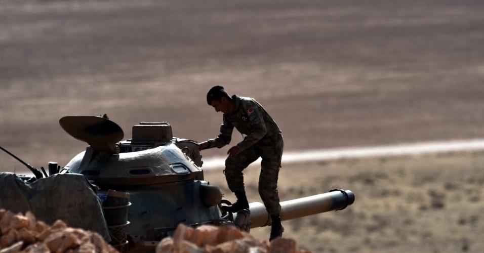 13.out.2014 - Um soldado turco desce um tanque do Exército, estacionado em uma colina, próximo à cidade síria de Kobani, na fronteira com a Turquia. O governo turco não concluiu nenhum novo acordo com os Estados Unidos para autorizar o acesso a suas bases aos aviões da coalizão internacional que bombardeiam os jihadistas do Estado Islâmico (EI) na Síria e no Iraque, afirmou uma fonte do governo turco