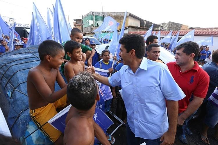 13.out.2014 - Helder Barbalho, candidato do PMDB ao governo do Pará, cumprimenta crianças durante caminhada no bairro de Barreiro, em Belém