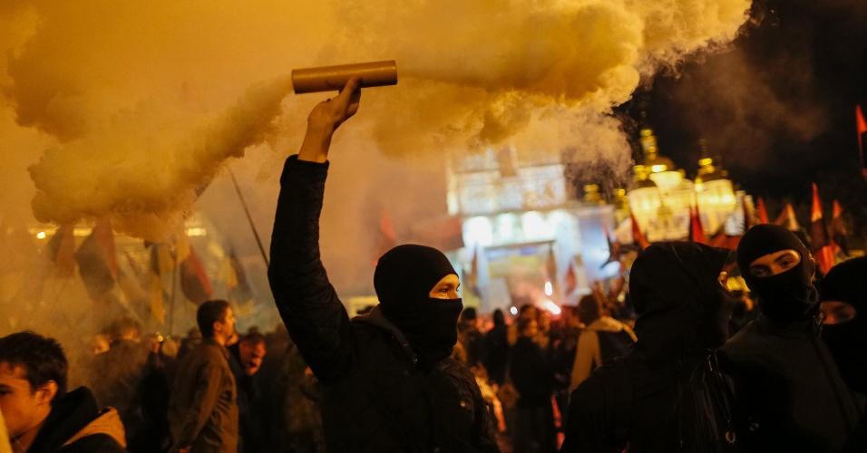 14.out.2014 - Combatentes do batalhão de Azov lançam sinalizadores durante marcha em Kiev, na Ucrânia, para comemorar o aniversário de 72 anos do UPA (Exército Insurgente Ucraniano), um movimento de resistência paramilitar formado em 1943 para lutar pela independência contra forças polonesas, soviéticas e alemãs no oeste da Ucrânia. O UPA é historicamente polêmico, pois é idolatrado por nacionalistas ucranianos, mas desprezado pela Rússia por colaborar com forças nazistas e lutar contra o Exército soviético