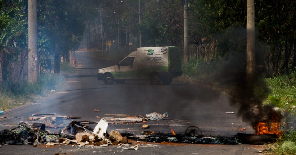 14.out.2014 - Moradores bloqueiam a avenida Celso Delledonnie, no Jardim Santo Antonio, em Campinas, interior de São Paulo, durante protesto nesta terça-feira (14). Bairros das regiões mais baixas da cidade sofrem com falta de água desde o fim de semana