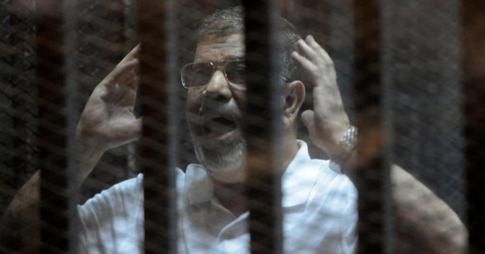 14.out.2014 - O presidente deposto do Egito Mohamed Mursi gesticula dentro da cela durante julgamento, na sede da polícia do Cairo. Mursi enfrenta várias acusações entre elas espionagem e encargos relacionados com o terrorismo, se for condenado pode ser sentenciado a morte
