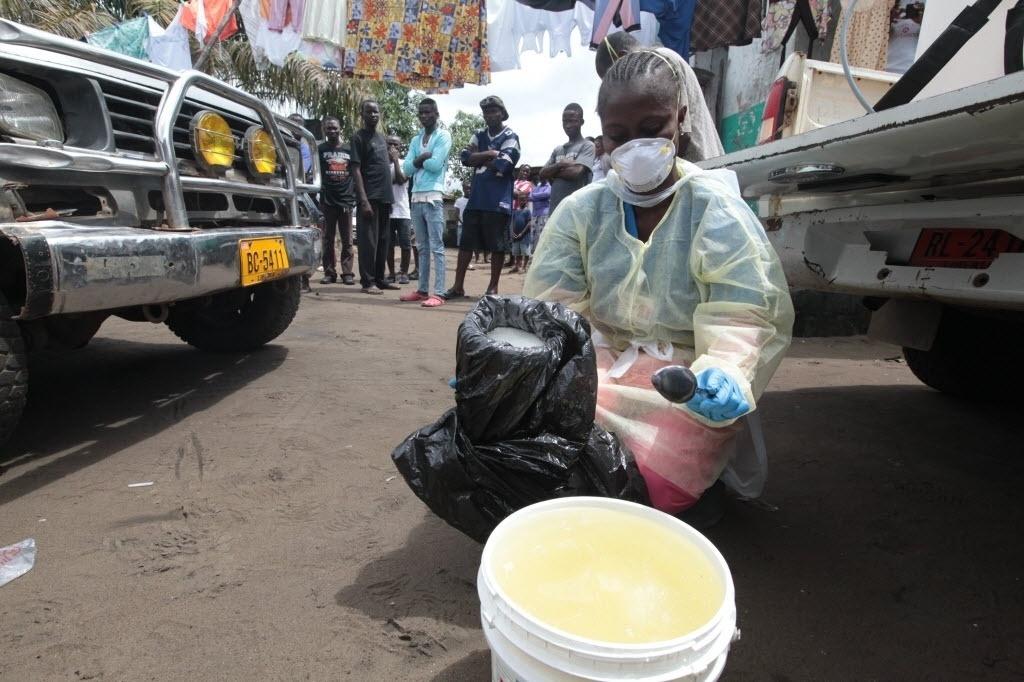 14.out.2014 - Trabalhadora de saúde mistura cloro com água para desinfetar residência de paciente que morreu de ebola, enquanto outros trabalhadores retiram o corpo do local, em Monróvia, na Libéria, nesta terça-feira (14)
