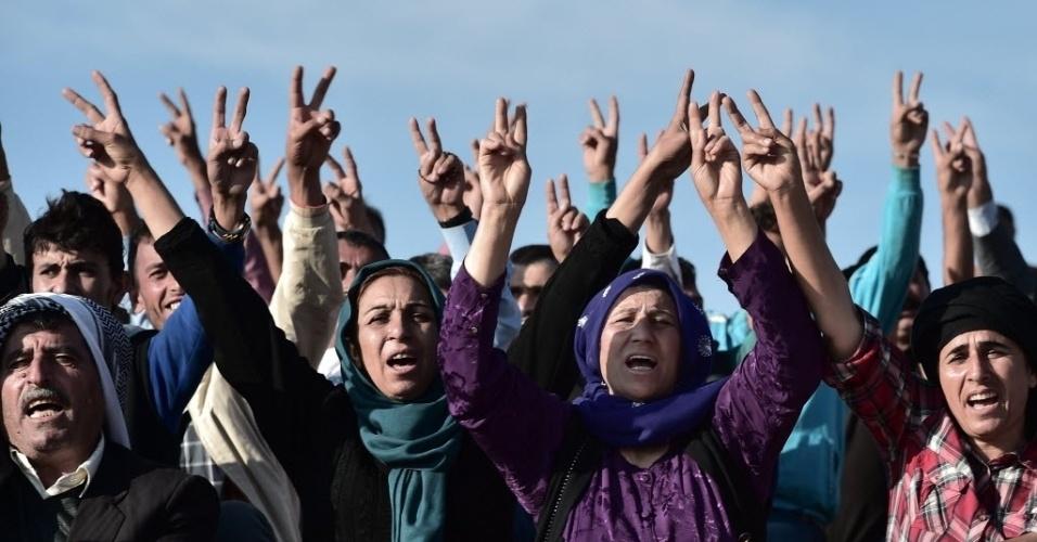 15.out.2014 - Homens e mulheres curdos fazem protesto em cima de uma colina em frente à cidade síria de Kobani. O grupo radical Estado Islâmico (EI) recuou de suas posições nesta quarta-feira no leste da cidade curdo-síria de Kobani, na fronteira com a Turquia, diante do avanço das forças curdas, que repeliram vários ataques dos jihadistas, informou o Observatório Sírio de Direitos Humanos (OSDH)