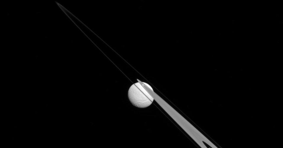 15.out.2014 - LUA PRESA NOS ANÉIS DE SATURNO - O registro da sonda Cassini mostra a Tétis, um dos satélites de Saturno, como se estivesse pendurada em um dos anéis do planeta. Como as partículas dos anéis são compostas principalmente por gelo, a lua só pode ser vista devido a uma lacuna clara, criada por uma outra lua do planeta, Daphnis, que não é vista na imagem