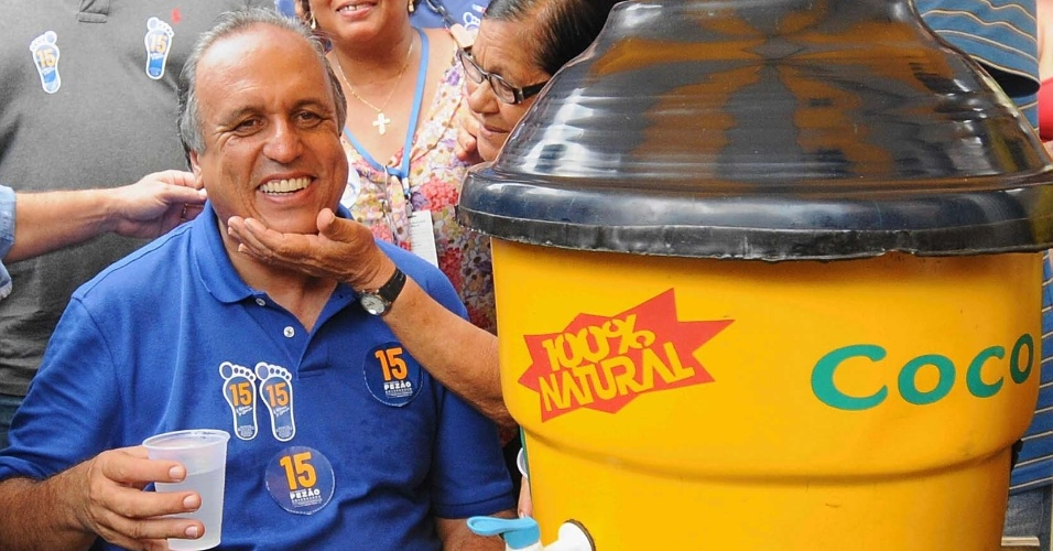 15.out.2014 - O governador do Estado do Rio de Janeiro e candidato à reeleição pelo PMDB, Luiz Fernando Pezão, senta para descansar e beber água de coco durante caminhada pelas ruas de Macaé, no norte fluminense