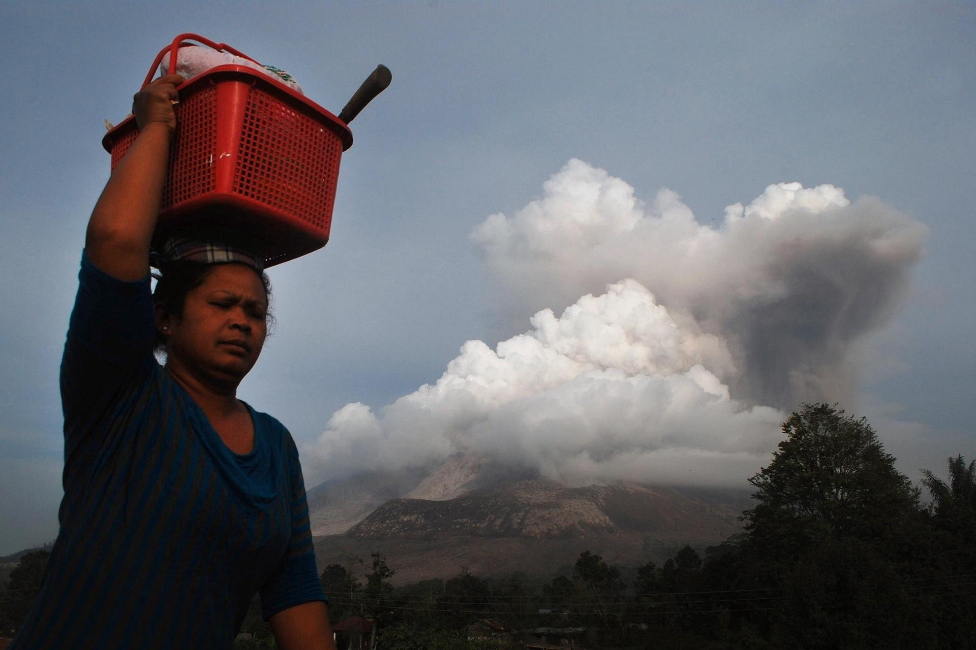 15.out.2014 - Uma mulher carrega seus pertences enquanto foge da erupção do vulcão Sinabung, no distrito de Karo, em Sumatra, na Indonésia, em foto tirada nessa terça-feira (14) e divulgada hoje (15). Em fevereiro, a erupção matou 17 pessoas e forçou mais de 33 mil a saírem de suas casas